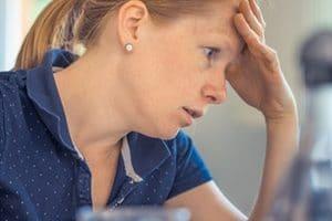 Mujer haciendo las cuentas de su casa y con actitud preocupada. www.auladefinanzaspersonales.com